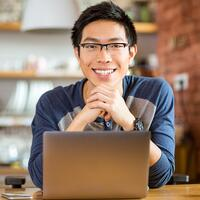 Portrait of positive asian male in glasses with laptop in cafe-1