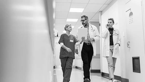 An image of a doctor with a nurse walking down a hallway
