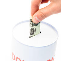 An image of a hand putting money in a donation box