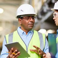 A man and woman wearing hardhats and carrying a tablet