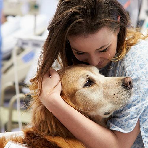 A woman in a hospital hugs a dog